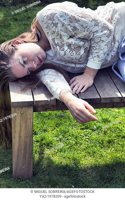 Woman Lying on Garden Bench