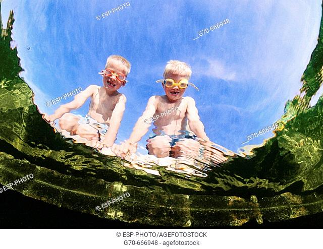 Boys with goggles looking into water