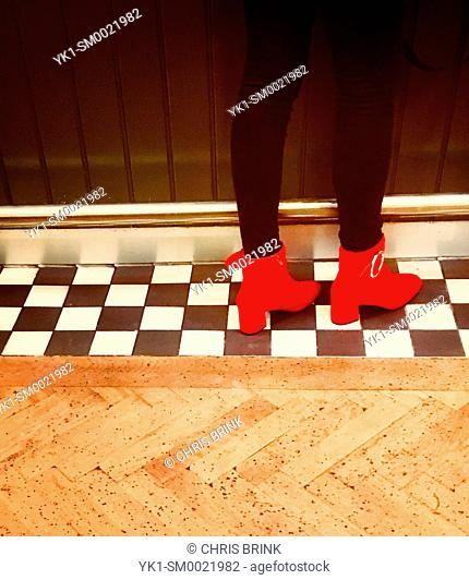 Woman wearing red shoes on checkered floor in a English pub waiting to be served