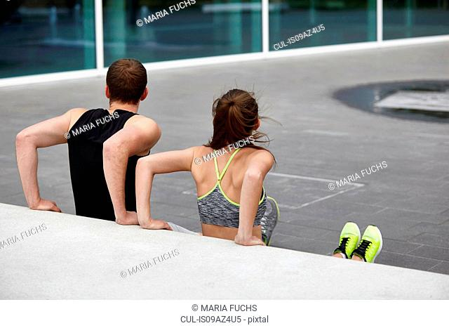 Young woman and man training, doing push ups against wall
