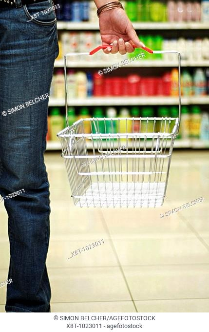 Young Woman Holding an Empty Shopping Basket in the Aisle of a Supermarket with Packed Shelves in the Background, Low Section