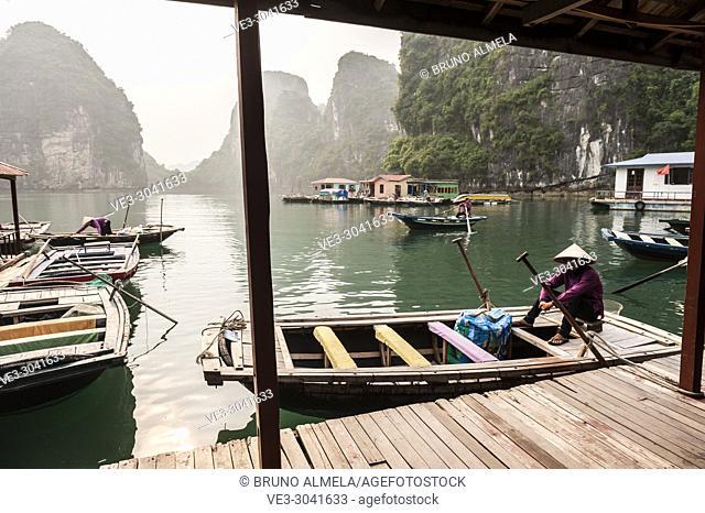 Vietnamese boatman in the karst landscape of Ha Long Bay, Quang Ninh Province, Vietnam. Ha Long Bay is a UNESCO World Heritage Site