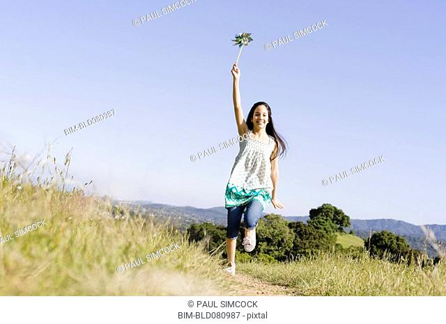 Hispanic girl running with pinwheel
