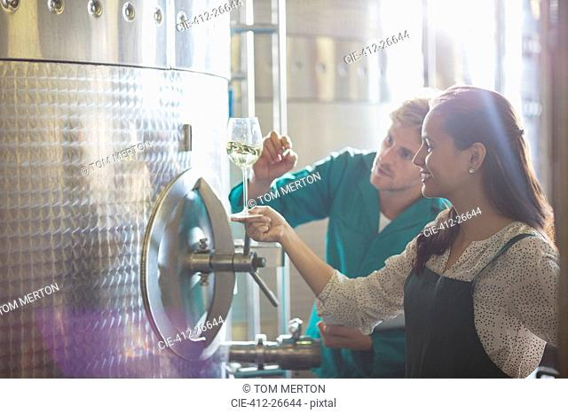Vintners examining white wine at stainless steel vat in winery cellar