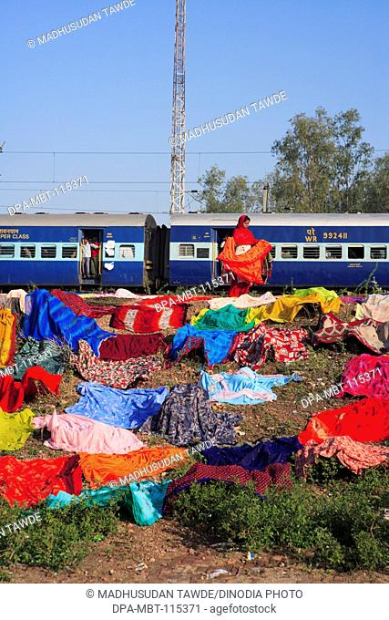 Woman drying clothes in open air in background of Indian Railway ; Agra ; Uttar Pradesh ; India