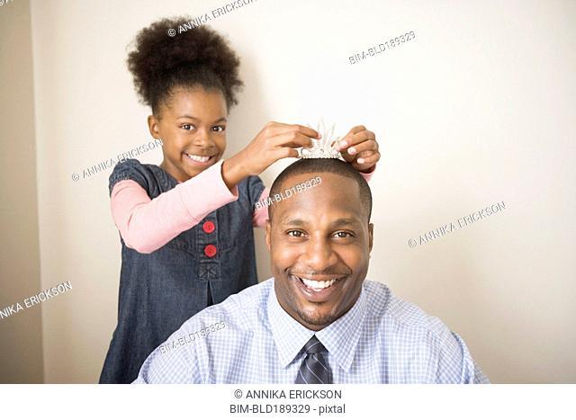 African father wearing daughter's tiara