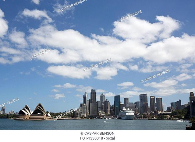 View of Sydney opera house and skyline against cloudy sky, Australia