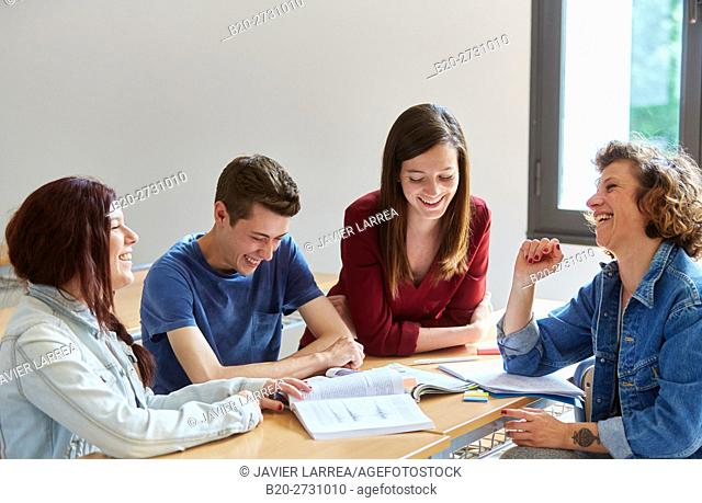 Students laughing at desk in classroom