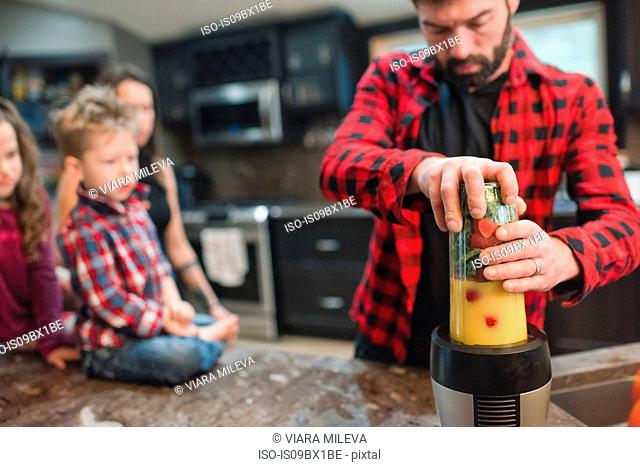 Mother and children watching father blend vegetables in kitchen