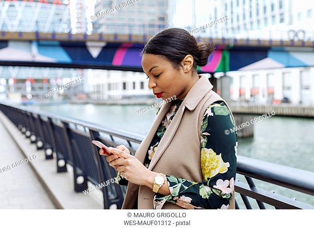 UK, London, fashionable businesswoman using smartphone