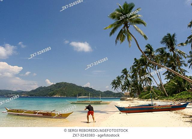 A tourist photographs boats moored in the white sand of Pangulasian Island. Palawan Philippines, Southeast Asia, Asia