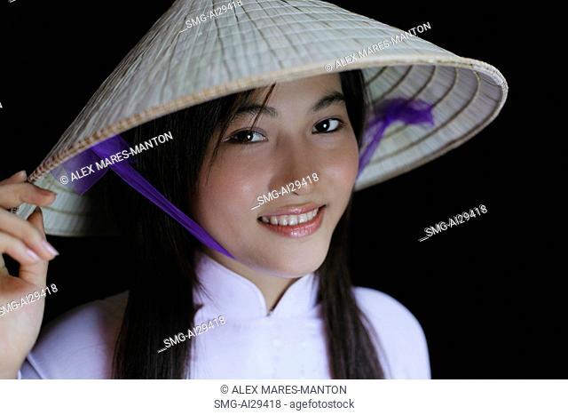 Young woman smiling, wearing Vietnamese hat