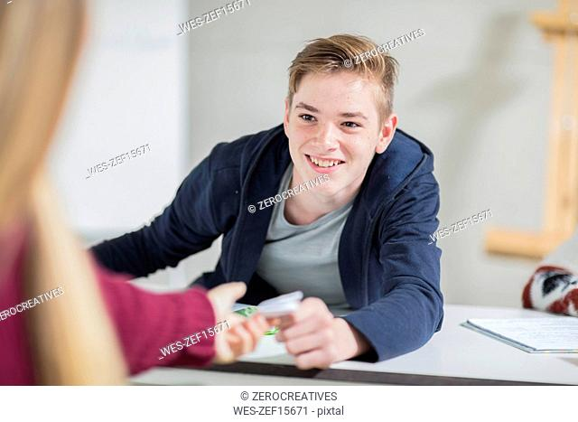 Smiling teenage boy passing a note to a girl in class