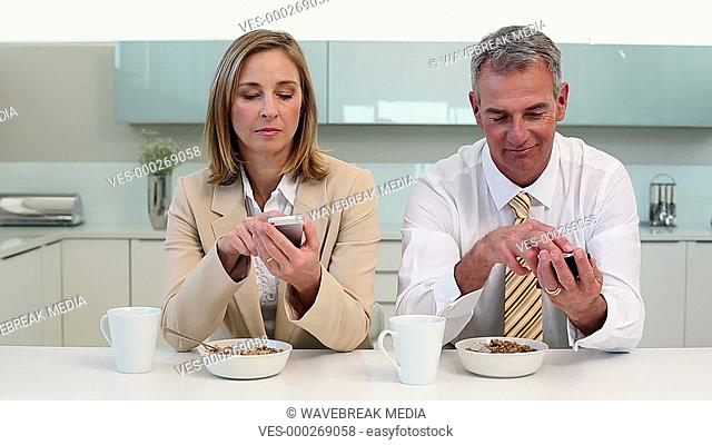 Couple having breakfast and texting before work