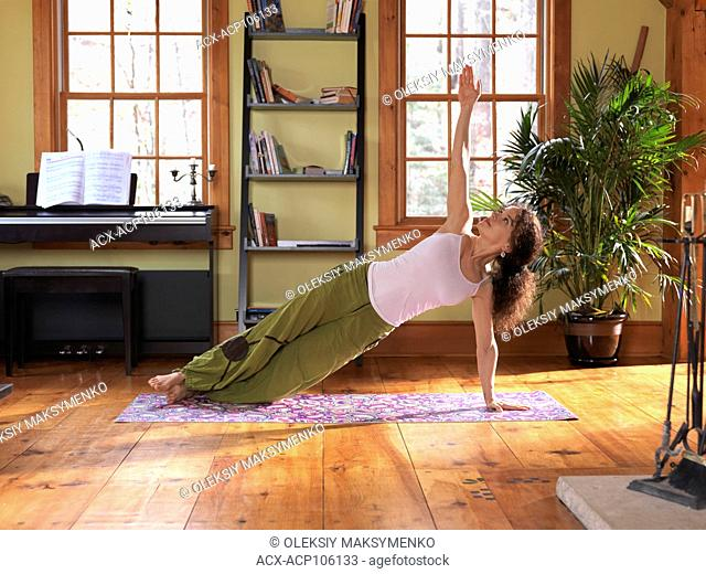 Young woman practicing yoga indoors at home in a living room on a bright sunny day