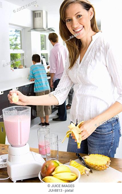 Woman making fruit smoothie in kitchen, smiling, portrait, father and son by kitchen sink in background