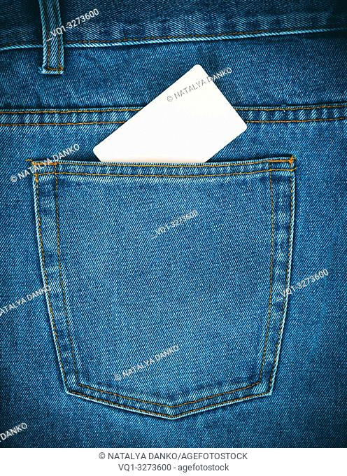 empty white paper card is in the back pocket of blue jeans, full frame