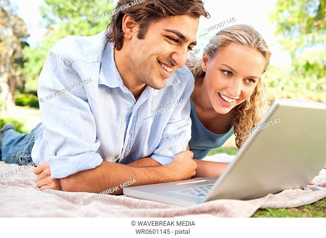 Couple lying on the lawn with their laptop