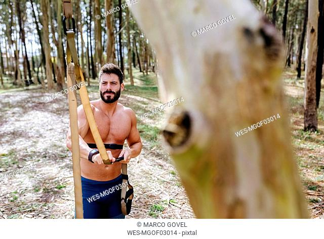 Barechested man preparing suspension traning outdoors