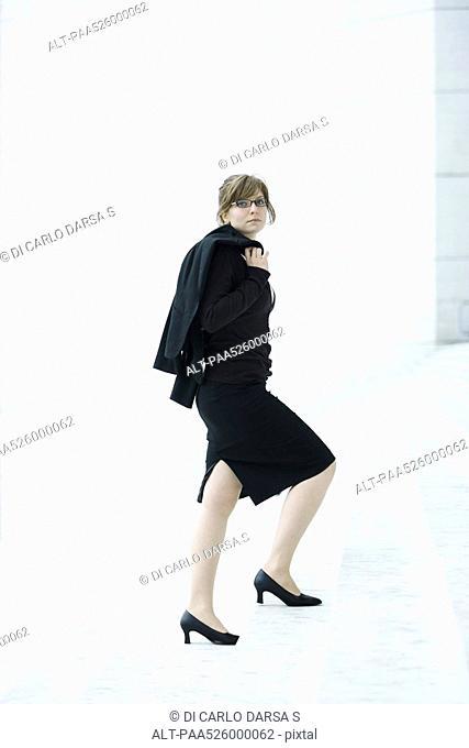Businesswoman, jacket on shoulder walking up steps