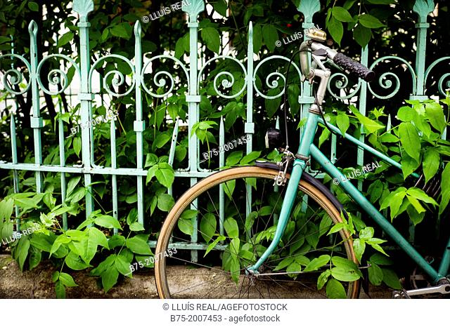 closeup of a bicycle parked at a gate of a garden in Paris, France