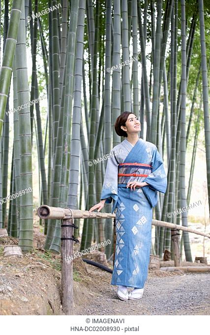 Young Japanese woman in kimono in bamboo forest