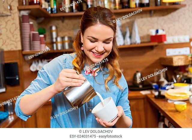 equipment, coffee shop, people and technology concept - barista woman pouring cream to cup of coffee at cafe bar or restaurant kitchen