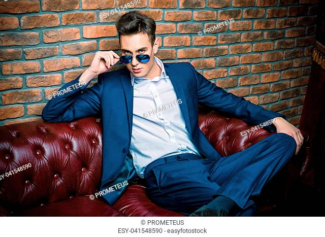 Imposing well dressed man in a luxurious apartments with classic interior. Luxury. Men's beauty, fashion