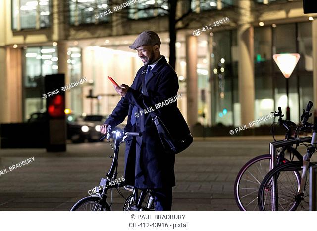 Businessman with smart phone and bicycle on urban street at night