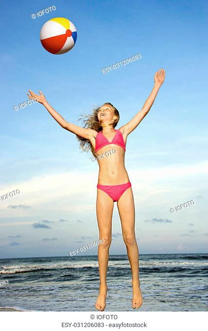Caucasian pre-teen girl playing with beachball on beach