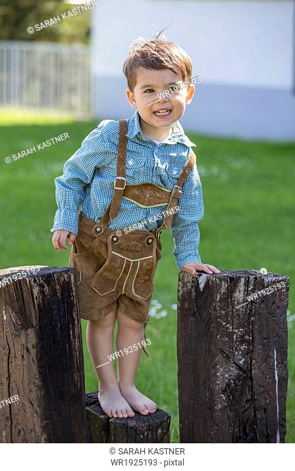 Little boy with leather pants climbing on wooden beams