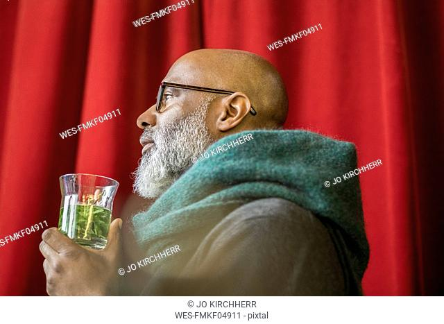 Profile of pensive man with glass of tea