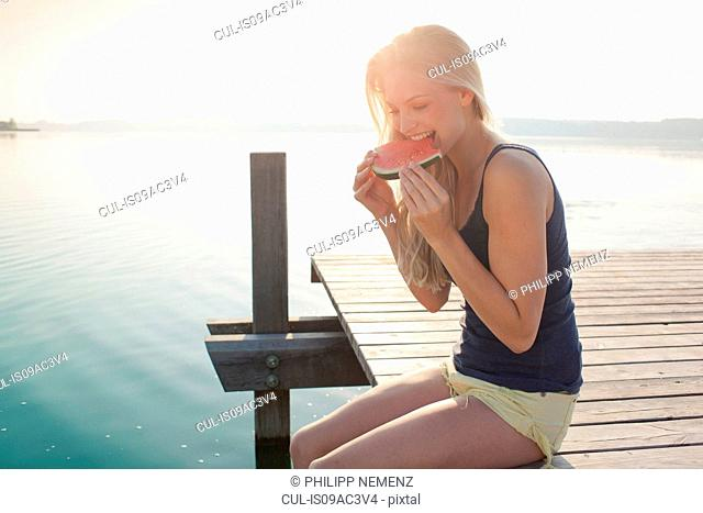 Portrait of young woman eating watermelon
