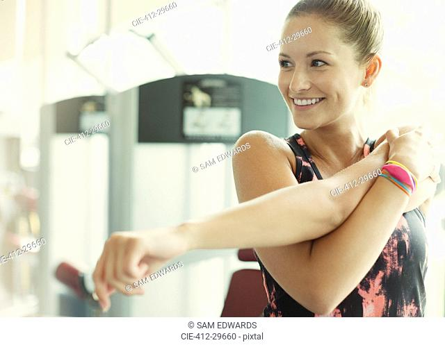 Smiling woman stretching arm at gym