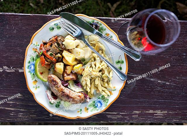 Meal served on a plate with a wineglass, Italy