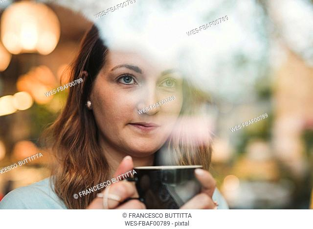 Young woman in a cafe drinking coffee behind windowpane