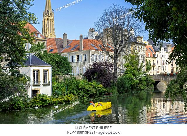 Paddle boat / pedal boat with tourists on the Moselle river in the city Metz, Moselle, Lorraine, France
