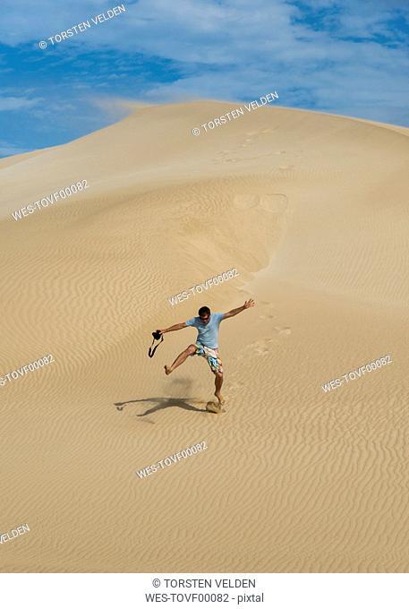 Australia, Port Lincoln, man running down sand dune