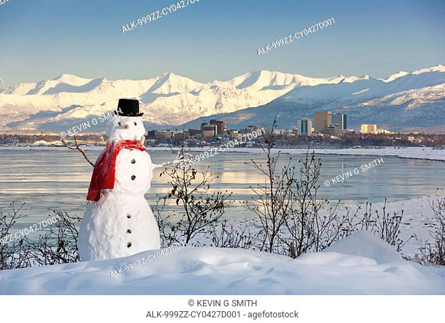 Scenic view of Chugach Mountains, Anchorage skyline, and Cook Inlet with a snowman in the foreground, Southcentral Alaska, Winter