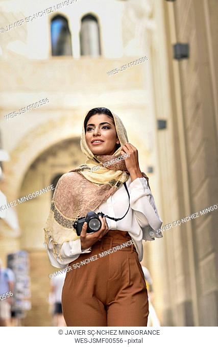 Spain, Granada, young Arab tourist woman wearing hijab, using camera during sightseeing in the city