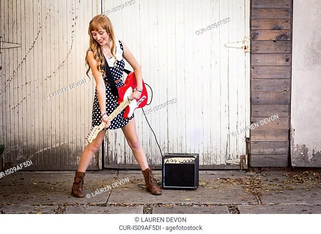 Young woman playing electric guitar outside garage