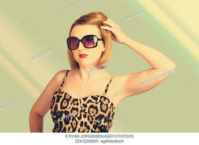1980 fashion image of a beautiful young sexy pin up woman wearing sunglasses with short auburn hairstyle on green salon background