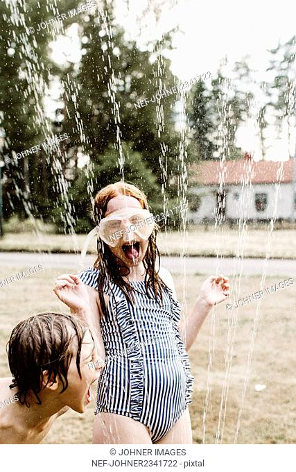 Cheerful girl wearing snorkel mask playing with brother