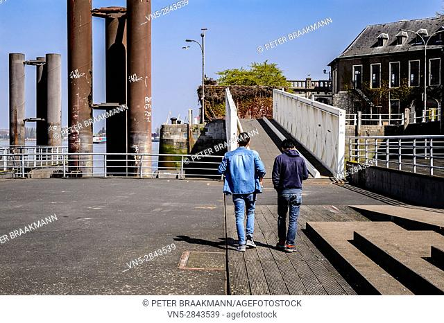 Antwerpen, Belgium - Two young are walking outdoor in the city, talking and chatting - working, successful