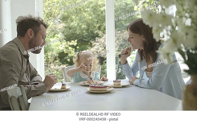 Family eating cake and enjoying at dining table