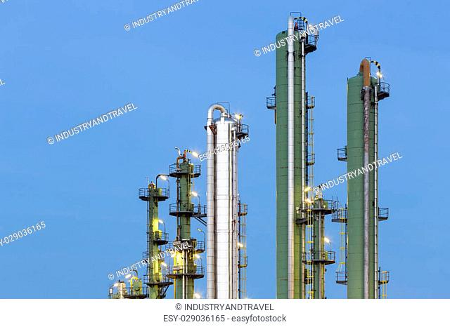 Detail of green and silver distillation towers in a chemical plant and refinery with night blue sky