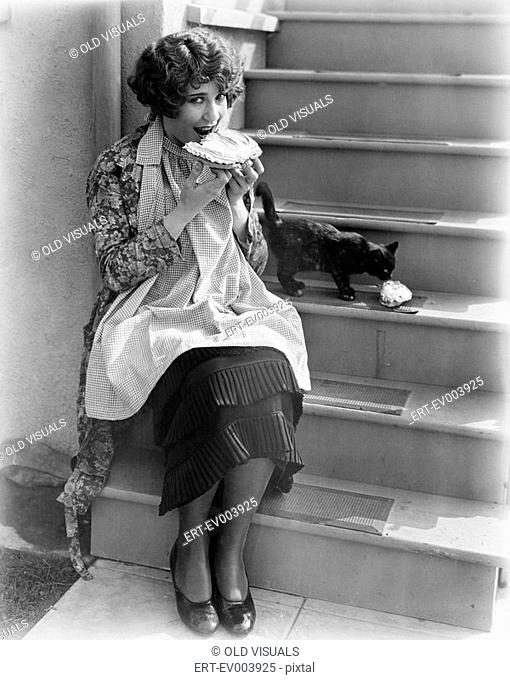 Woman sharing pie with cat All persons depicted are not longer living and no estate exists Supplier warranties that there will be no model release issues