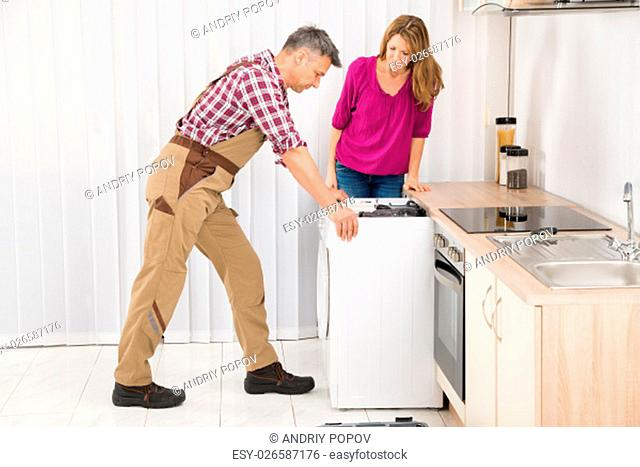 Mature Woman Looking At Male Worker Repairing Washing Machine In Kitchen