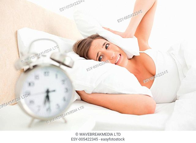 Woman covering her ears with a pillow