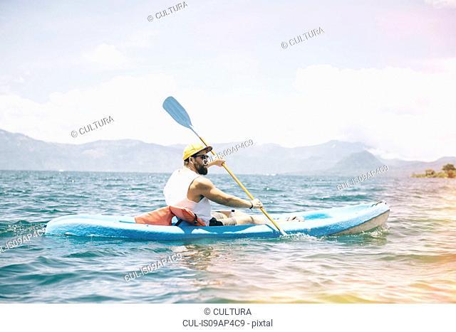 Young man kayaking on Lake Atitlan, Guatemala